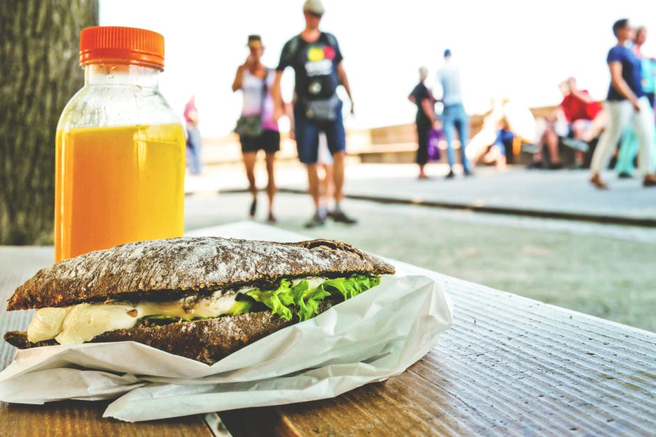 A bottle of orange juice and a sandwich on a bench at a food festival