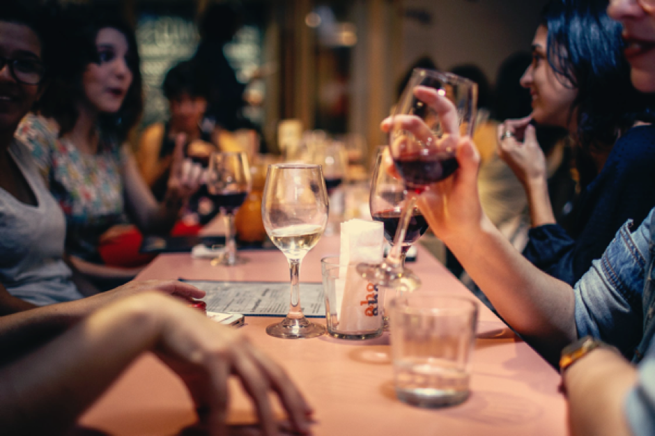 A table in a restaurant full of people talking and drinking wine