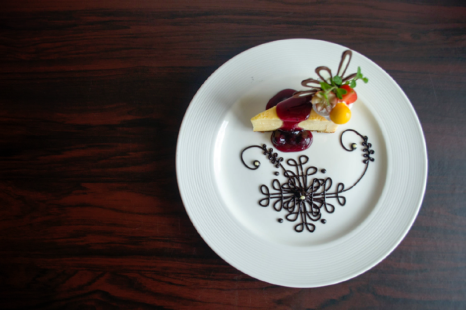 A dessert with a beautiful pattern created out of chocolate sauce