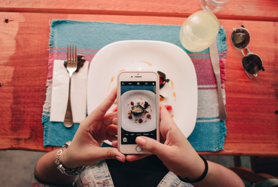 A person sitting down to dinner taking a picture of their food using their phone